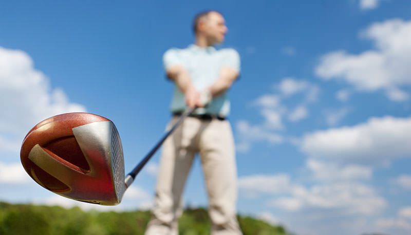 man with golf clubs