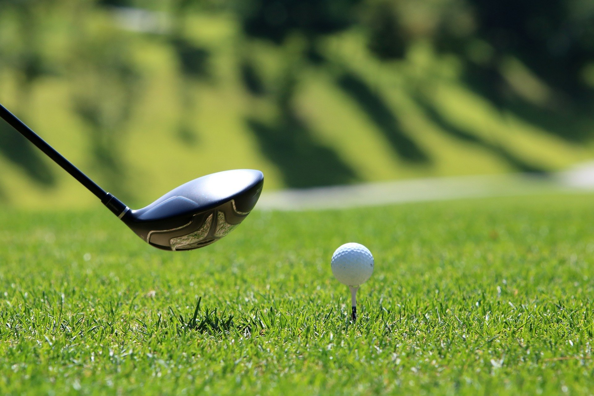 A golf club in the grass, in front of a kirkland golf ball