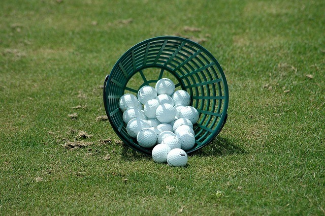 a tippped over basket of golf balls