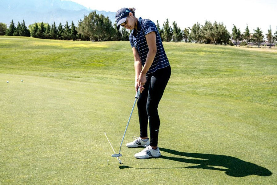 Woman playing golf demonstrating what is a fade in golf