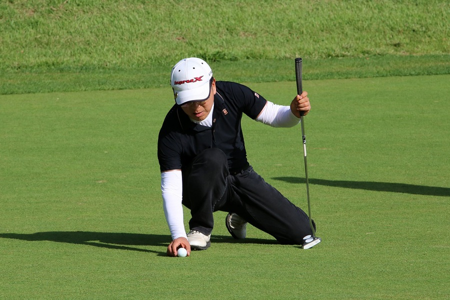 Golfer positioning a golf ball and wearing a white hat